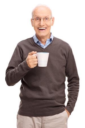 hombres maduros: Tiro vertical de una alegría mayor que sostiene una taza de café blanco y mirando a la cámara aislada en el fondo blanco