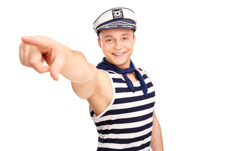 sailors: Young cheerful sailor pointing forward with his finger and looking at the camera isolated on white background