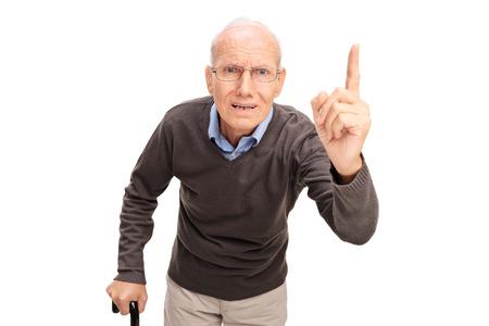 personas discutiendo: Hombre mayor enojado con un regaño de caña y haciendo un gesto con su dedo aislado en el fondo blanco Foto de archivo