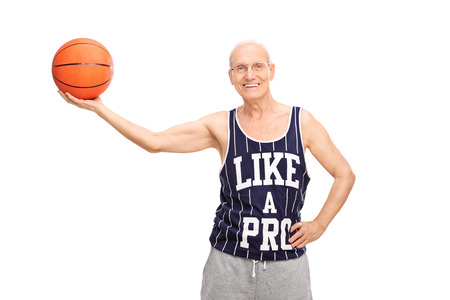 Cheerful senior man in a sports jersey holding a basketball and looking at the camera isolated on white background photo