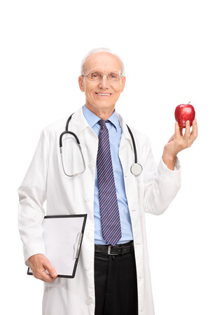 Vertical shot of a mature healthcare professional holding a shiny red apple and looking at the camera isolated on white background photo