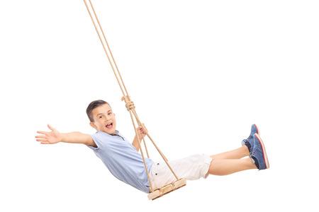 Joyful kleiner Junge schwingt auf einer Schaukel und Gestik Glück isoliert auf weißem Hintergrund