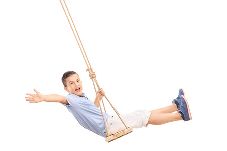 columpio: Niño pequeño alegre balanceándose en un columpio y gesticulando felicidad aislado en fondo blanco Foto de archivo