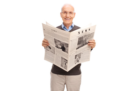 oude krant: Senior gentleman holding a newspaper and looking at the camera isolated on white background