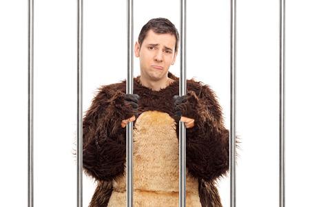 carcel: Studio foto de una joven triste en un traje de oso de pie detr�s de las rejas en una celda aislada sobre fondo blanco