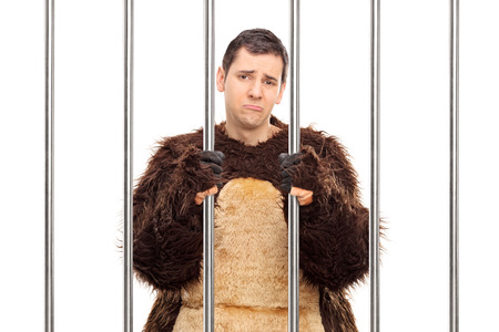 Studio shot of a sad young man in a bear costume standing behind bars in a cell isolated on white background photo