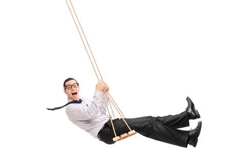 hombre sentado: Hombre joven encantada balanceándose en un columpio y mirando a la cámara aislada en el fondo blanco Foto de archivo