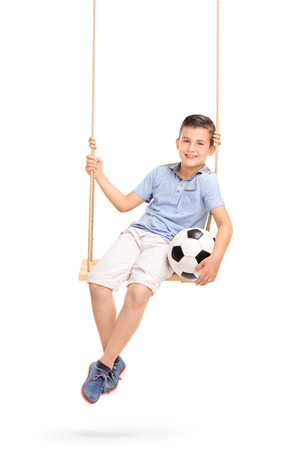 boy ball: Vertical shot of a relaxed and joyful little boy holding a football seated on a wooden swing isolated on white background