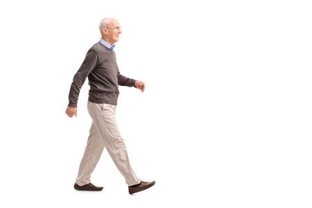 bewegung menschen: In voller Länge Profil Schuss von einem lässig älterer Mann zu Fuß und lächelnd isoliert auf weißem Hintergrund
