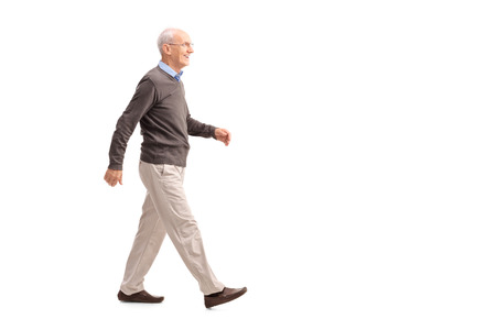 profil: Pełny profil długość strzał przypadkowy starszego mężczyzny chodzenia i uśmiecha się na białym tle