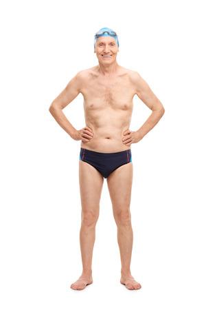 hombre sin camisa: Retrato de cuerpo entero de una persona mayor sin camisa en traje de baño negro y azul gorro de baño mirando a la cámara y sonriente aislados sobre fondo blanco