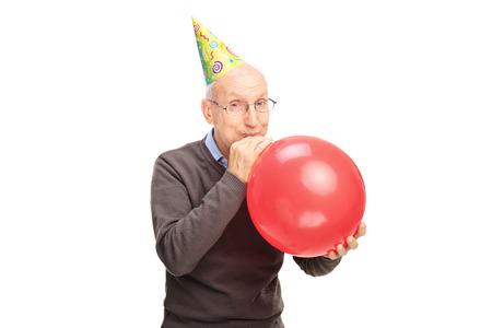Vrolijke senior met een feest hoed op zijn hoofd opblazen van een ballon en kijken naar de camera op een witte achtergrond