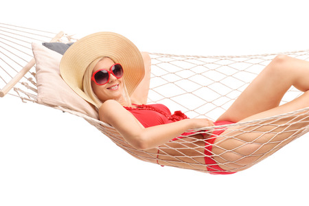 Beautiful blond woman with a stylish hat and a red bathing suit lying in a hammock and smiling isolated on white background photo