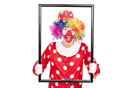 big picture: Male clown holding a big picture frame and posing behind it isolated on white background Stock Photo