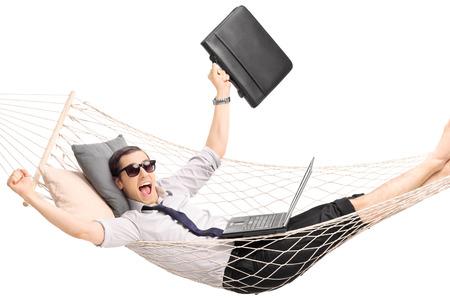 ラップトップでの彼のラップと白で隔離ジェスチャー喜びハンモックに横たわる青年実業家 写真素材