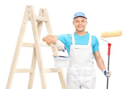 pintor de casas: Joven pintor de brocha gorda masculina con un mono blanco limpio sostiene un rodillo de pintura y apoyado en una escalera de madera aislada sobre fondo blanco
