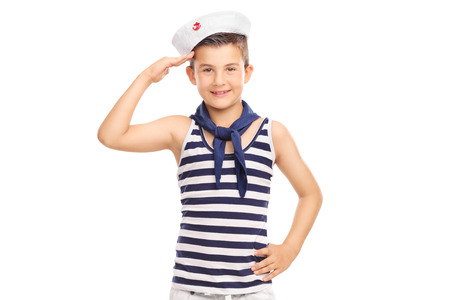 Cute little kid in a sailor uniform saluting towards the camera isolated on white background