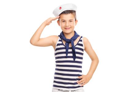marinero: Niño lindo en un uniforme de marinero saludando hacia la cámara aislada en el fondo blanco