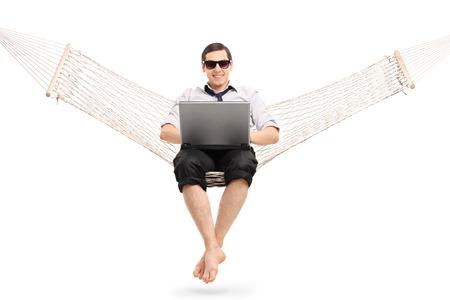 relajado: Empresario joven relajado sentado en una hamaca y trabajar en la computadora portátil aislados en fondo blanco