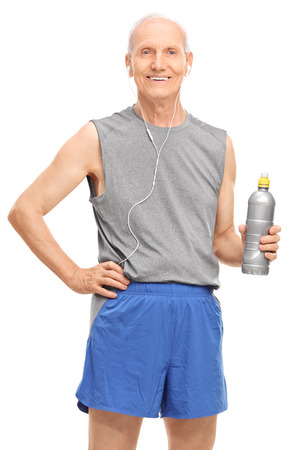 Vertical shot of a senior man in sportswear listening music on headphones and holding a water bottle isolated on white background photo