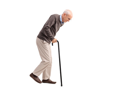 Studio shot of an exhausted old man walking with a cane isolated on white background Archivio Fotografico