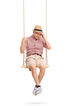 remembering: Vertical shot of a depressed senior man sitting on a swing and remembering something isolated on white background