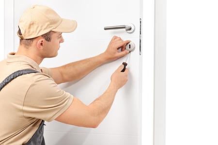 puerta: Estudio tirado de un cerrajero var�n joven instalar una cerradura en una puerta blanca con un destornillador aislado en fondo blanco