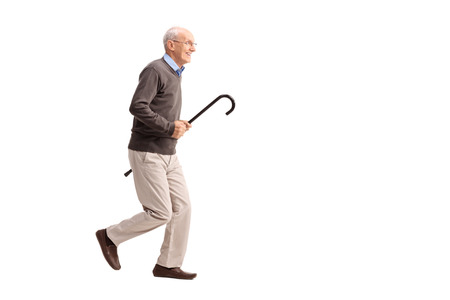 vital: Full length portrait of a joyful senior gentleman carrying a cane in his hand and running isolated on white background