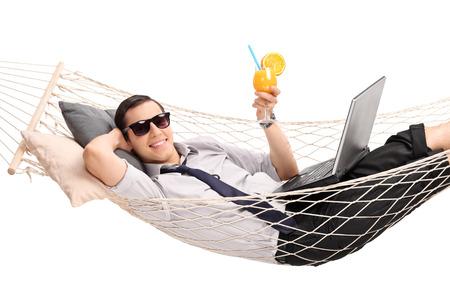 hammock: Joven empresario acostado en una hamaca con un ordenador port�til en su regazo y beber un c�ctel de naranja aislada sobre fondo blanco