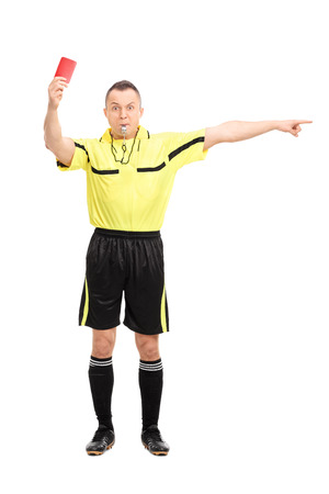 Full length portrait of an angry football referee showing a red card and pointing with his hand isolated on white background