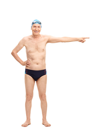 trunk: Full length portrait of a senior man in black swim trunks pointing with his hand towards right and looking at the camera isolated on white background