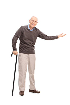 persona de la tercera edad: Retrato de cuerpo entero de una persona mayor con un bastón sonriendo y haciendo un gesto con la mano aisladas sobre fondo blanco Foto de archivo