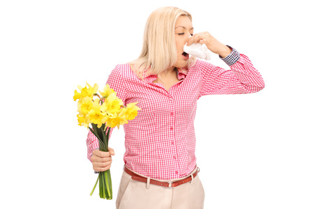 allergic reaction: Young blond woman having an allergic reaction to flowers and blowing her nose isolated on white background