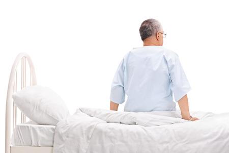 cama: Posterior disparo de estudio de opinión de un paciente de alto nivel en una bata de hospital sentado en una cama de hospital aislado en fondo blanco