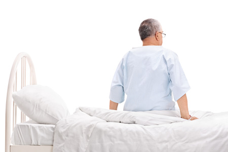 male senior adult: Rear view studio shot of a senior patient in a hospital gown sitting on a hospital bed isolated on white background