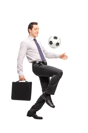 juggling: Full length portrait of a young businessman holding a briefcase and juggling a football isolated on white background