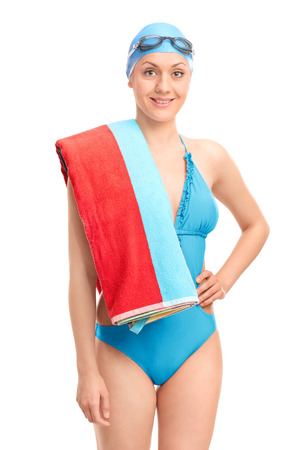 female person: Young female swimmer in a blue swimsuit carrying a towel over her shoulder and looking at the camera isolated on white background Stock Photo