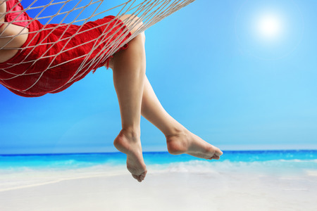 day break: Close-up on the legs of a woman lying in a hammock on a beach by the open sea Stock Photo