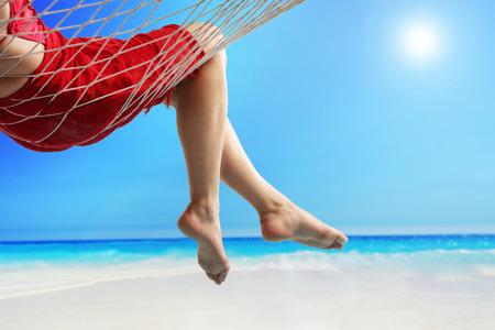 hamaca: Primer plano de las piernas de una mujer acostada en una hamaca en una playa junto al mar abierto