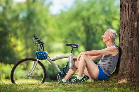 ancianos felices: El hombre mayor activo de escuchar música en los auriculares sentado junto a un árbol en un parque