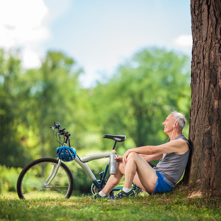 senior old: Senior cyclist sitting by a tree in a park with a water bottle in his hand and listening to music on headphones shot with tilt and shift lens Stock Photo