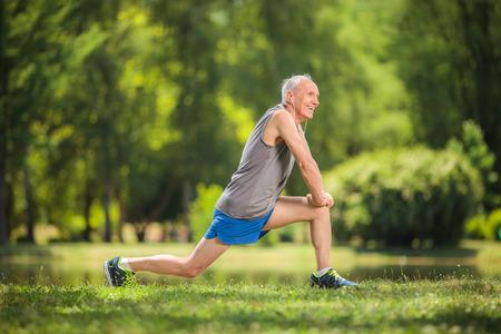 Profiel shot van een senior in sportkleding doet strekoefeningen in een park en het luisteren naar muziek op de koptelefoon Stockfoto