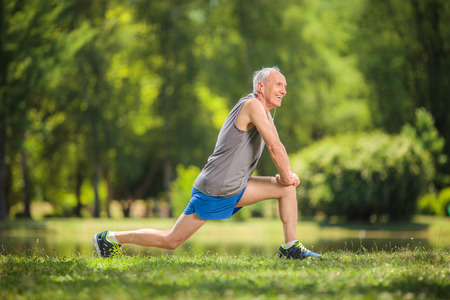 man in field: Profile shot of a senior in sportswear doing stretching exercises in a park and listening to music on headphones Stock Photo