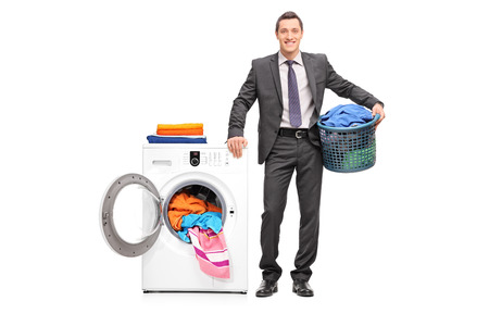 launder: Full length portrait of a young businessman holding a laundry basket and posing next to a washing machine isolated on white background
