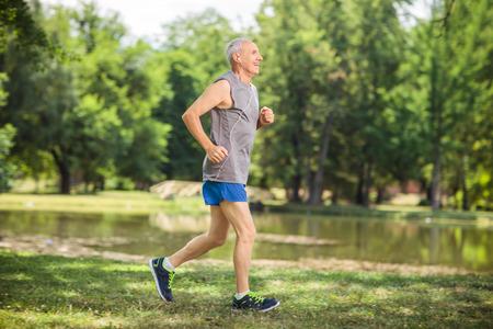 actief luisteren: Profiel schot van een actieve senior joggen in een park en het luisteren naar muziek op de koptelefoon Stockfoto