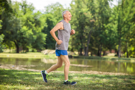 active listening: Profile shot of an active senior jogging in a park and listening to music on headphones Stock Photo