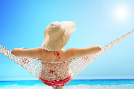 Rear view of a woman in a red swimsuit with a stylish hat lying on a hammock on a beach by the sea Stock Photo