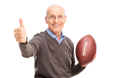 Studio shot of a cheerful senior holding an American football and giving a thumb up isolated on white background