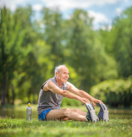 stretches: Cheerful senior doing stretching exercises in park by a pond shot with tilt and shift lens
