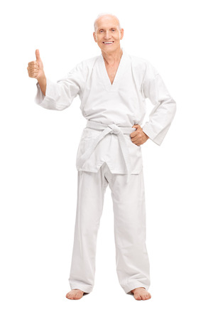 posing  agree: Full length portrait of a senior man in a white kimono giving a thumb up and smiling isolated on white background